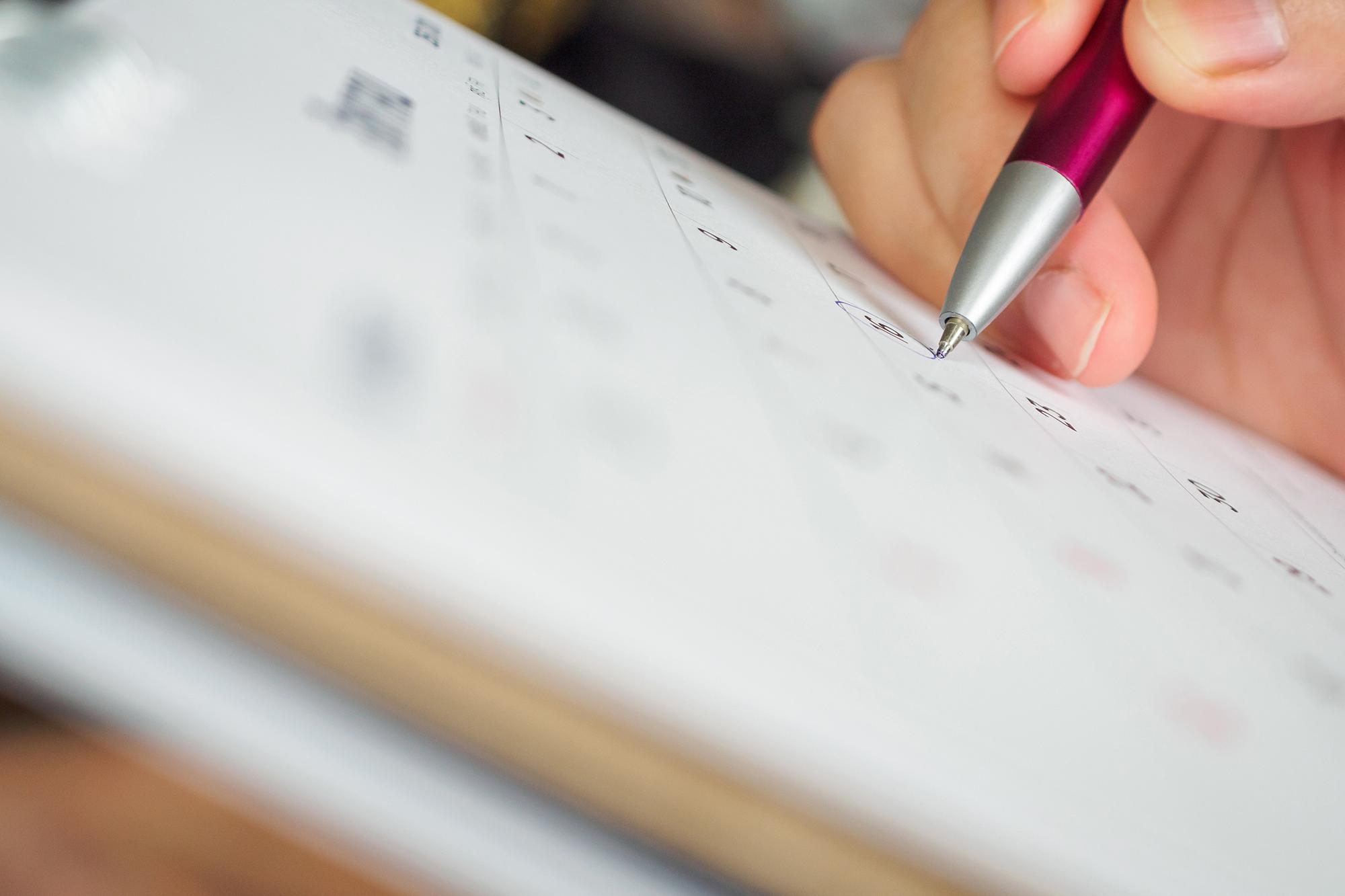Stift kreist Datum auf Kalender ein | c iStock/Kwangmoozaa